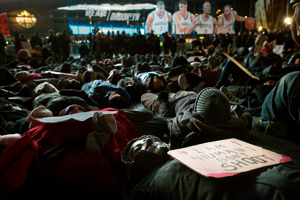 ". Protestors participate in a ""die-in\"" during a demonstration outside the Barclays Center against a grand jury\'s decision not to indict the police officer involved in the death of Eric Garner, Monday, Dec. 8, 2014, in the Brooklyn borough of New York. Britain\'s Prince William, the Duke of Cambridge, and Kate, Duchess of Cambridge, not pictured, attended a NBA basketball game between the Cleveland Cavaliers and the Brooklyn Nets at Barclays Center on Monday. (AP Photo/John Minchillo)"