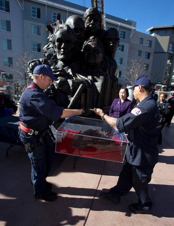 """. Oakland firefighters carry a piece of steel from the twin towers of the World Trade Center, to be placed inside Mario Chiodo\'s \""""Remember Them\"""" statue, at a ceremony to dedicate the final section of Chiodo\'s paean to heroes of civil rights and humanity, Thursday, Feb. 21, 2013 in Oakland Calif. (D. Ross Cameron/Staff)"""