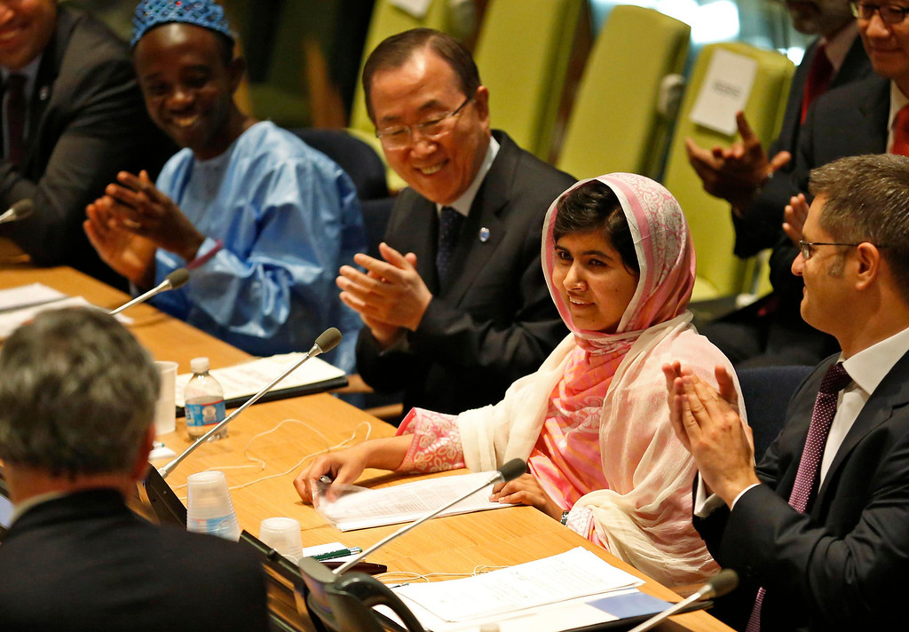 . Malala Yousafzai (2nd R), is introduced before her first speech since the Taliban in Pakistan tried to kill her for advocating education for girls, at the United Nations Headquarters in New York, July 12, 2013. Wearing a pink head scarf, Yousafzai told U.N. Secretary-General Ban Ki-moon (3rd R) and nearly 1,000 students from around the world attending a Youth Assembly at U.N. headquarters in New York that education was the only way to improve lives. REUTERS/Brendan McDermid