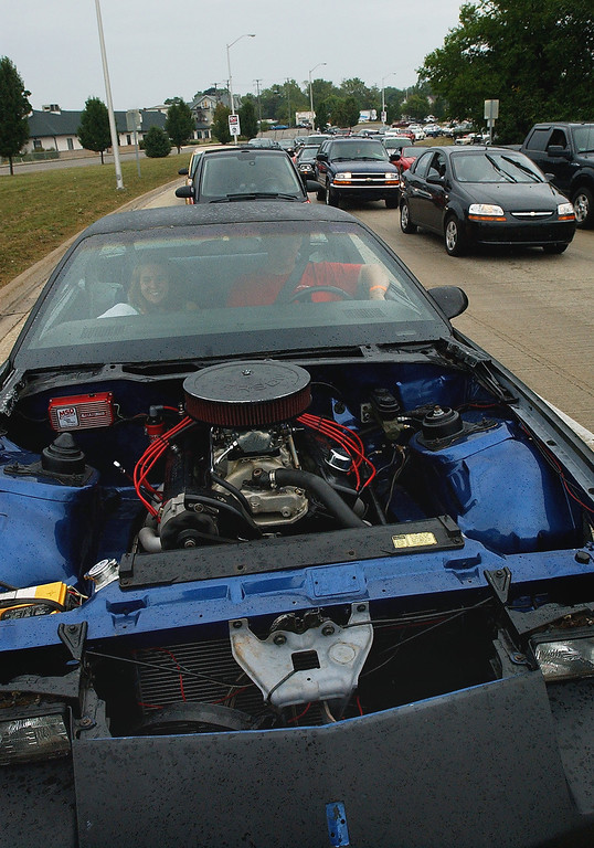 . A motorist drives a 1984 Camaro, with no engine hood, as he makes the loop on Woodward, during the Dream Cruise.  Photo taken on Saturday, August 21, 2010, in Pontiac, Mich.  (The Oakland Press/Jose Juarez)