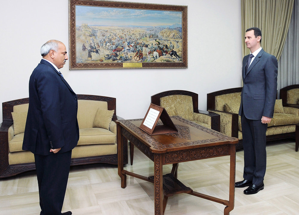 . In this photo released by the Syrian official news agency SANA,Mohammed Zaal al-Ali, left, is sworn in as governor of Hasaka province, by Syrian President Bashar Assad, right, in Damascus, Syria, Thursday, March 28, 2013. (AP Photo/SANA)