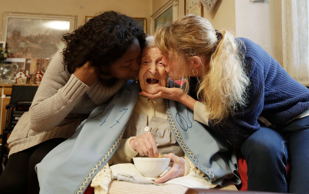 . Emma Morano, 117 years hold, is kissed by her caretakers Malgorzat Ceglinska, right, and Yamilec Vergara, in the day of her birthday in Verbania, Italy, Tuesday, Nov. 29, 2016.  At 117 years of age, Emma is now the oldest person in the world and is believed to be the last surviving person in the world who was born in the 1800s, coming into the world on Nov. 29, 1899. (AP Photo/Antonio Calanni)