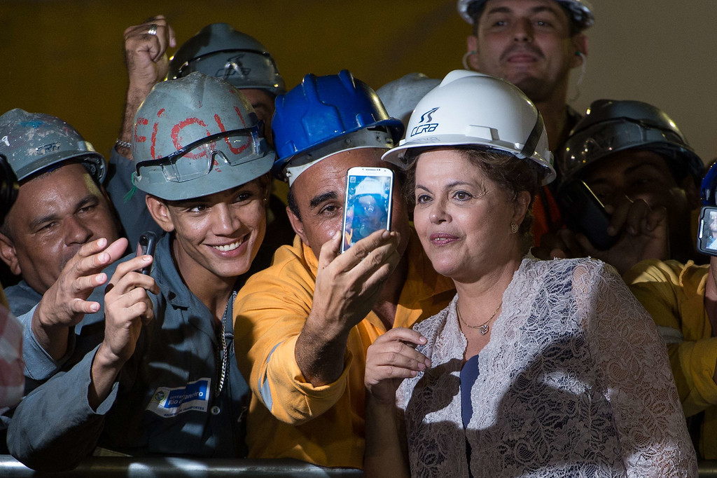 . Brazilian President Dilma Rousseff (R) poses with workers during a visit to the construction site of the metro station Sao Conrado (Line 4) in Rio de Janeiro, Brazil, on April 2, 2014.  AFP PHOTO / YASUYOSHI CHIBA/AFP/Getty Images