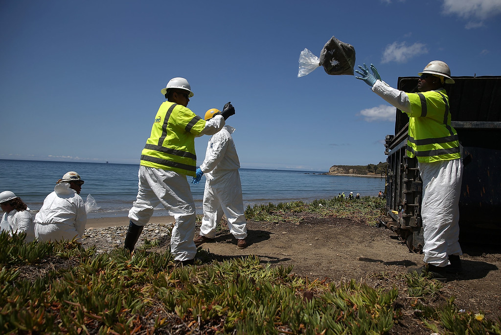 . Workers toss bags of oil contaminated sand as they clean oil from the beach at Refugio State Beach on May 22, 2015 in Goleta, California. California Gov. Jerry Brown declared a State of Emergency after over 100,000 gallons of oil spilled from an abandoned pipeline on the land near Refugio State Beach, spreading over about nine miles of beach within hours. The largest oil spill ever in U.S. waters at the time occurred in the same section of the coast in 1969 where numerous offshore oil platforms can be seen, giving birth to the modern American environmental movement. (Photo by Justin Sullivan/Getty Images)