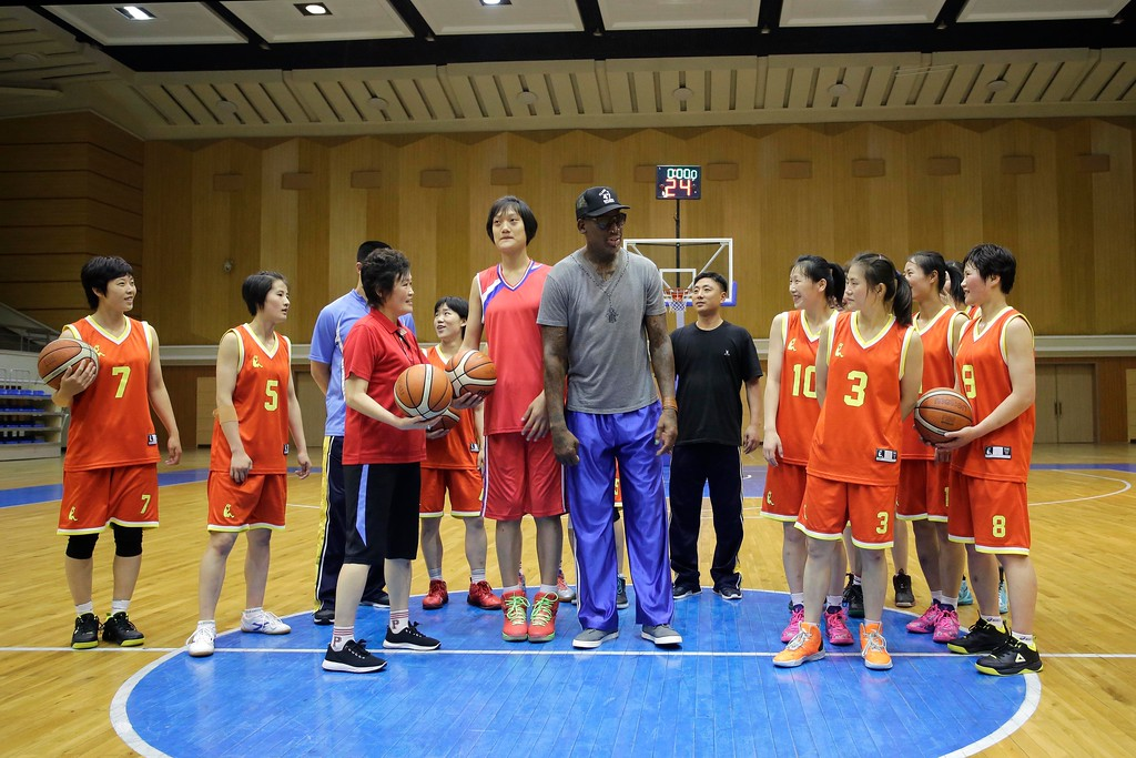". Former NBA basketball star Dennis Rodman, center right, talks to North Korea\'s Pothonggang womens basketball team during his visit to Chongjong Street basketball gymnasium on Wednesday, June 14, 2017, in Pyongyang, North Korea. Rodman began sightseeing in Pyongyang on Wednesday during a trip he said he hoped would ""open a door\"" for his former \""Celebrity Apprentice\"" boss, President Donald Trump. (AP Photo/Kim Kwang Hyon)"