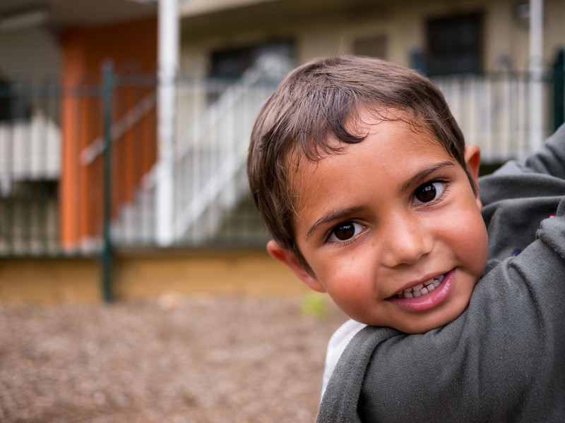 This photo shows a five-year-old Aboriginal boy in an urban setting in the Greater City of Melbourne, Australia.  The photo was made in the playground of a housing estate.