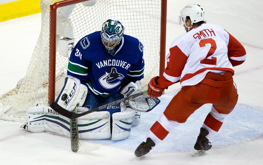. Vancouver Canucks goalie Ryan Miller, left, stops Detroit Red Wings\' Brendan Smith during the second period of an NHL hockey game in Vancouver, British Columbia on Saturday, Jan. 3, 2015. (AP Photo/The Canadian Press, Darryl Dyck)