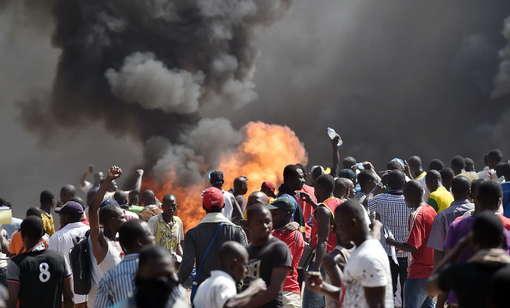 . People stand in front of smoke rising from the Burkina Faso\'s Parliament, where demonstrators set cars on fire parked in a courtyard of the Parliament, on October 30, 2014 in Ouagadougou, as they protest at plans to change the constitution to allow President Blaise Compaore to extend his 27-year rule.  Police had fired tear gas on protesters to try to prevent them from moving in on the National Assembly building in the capital Ouagadougou ahead of a vote on the controversial legislation.    But about 1,500 people managed to break through the security cordon and were ransacking parliament, according to AFP correspondents. Protesters ransacked offices, setting fire to documents and stealing computer equipment, and set fire to cars outside. ISSOUF SANOGO/AFP/Getty Images