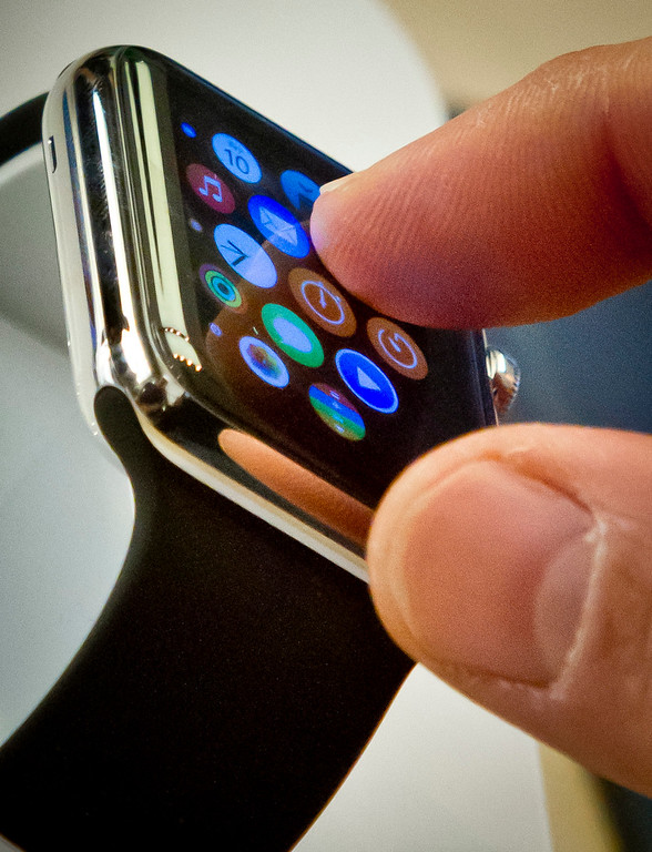 . A customer examines Apple\'s new watch, Friday, April 10, 2015, in New York. Apple has started taking orders for the watch on its website and the Apple Store app. Currently, that\'s the only way Apple is selling the watch, with shipments scheduled to start April 24.  (AP Photo/Bebeto Matthews)