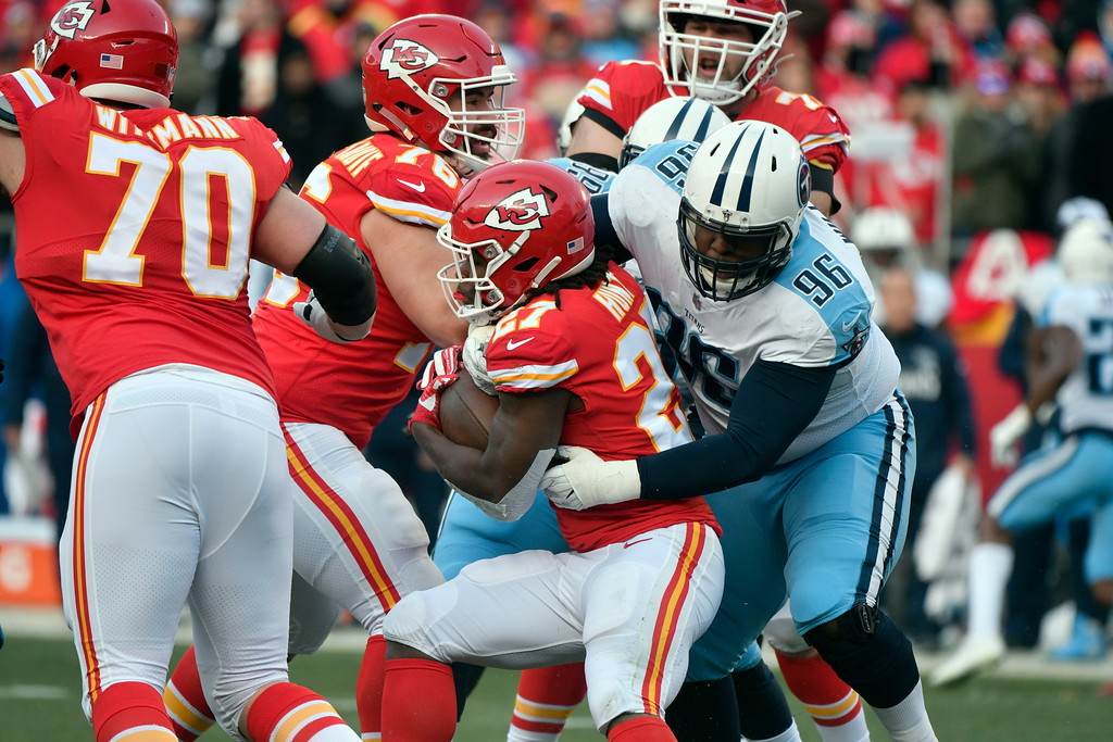 . Kansas City Chiefs running back Kareem Hunt (27) is tackled by Tennessee Titans nose tackle Sylvester Williams (96) during the first half of an NFL wild-card playoff football game, in Kansas City, Mo., Saturday, Jan. 6, 2018. (AP Photo/Ed Zurga)