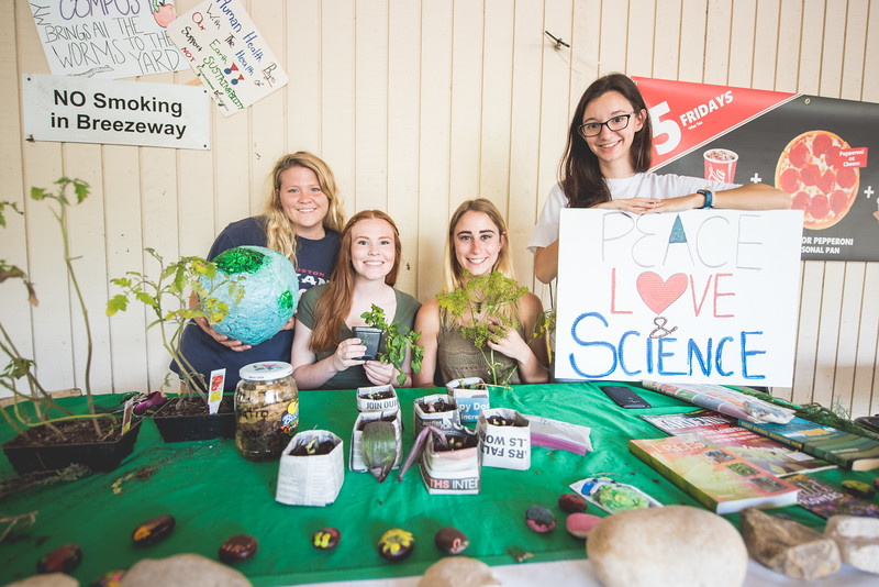 Elise Rother (left), Claire Berger, Breanna Hild, and Maria Cherry set up in the breezeway in celebration of Earth Day.