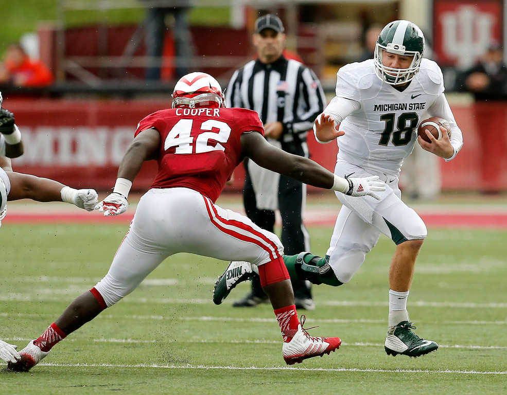 . Michigan State quarterback Connor Cook (18) tries to evade Indiana linebacker David Cooper (42)  during the first half of an NCAA college football game in Bloomington, Ind., Saturday, Oct.ober 18, 2014. Michigan State won the game 56-17. (AP Photo/Sam Riche)