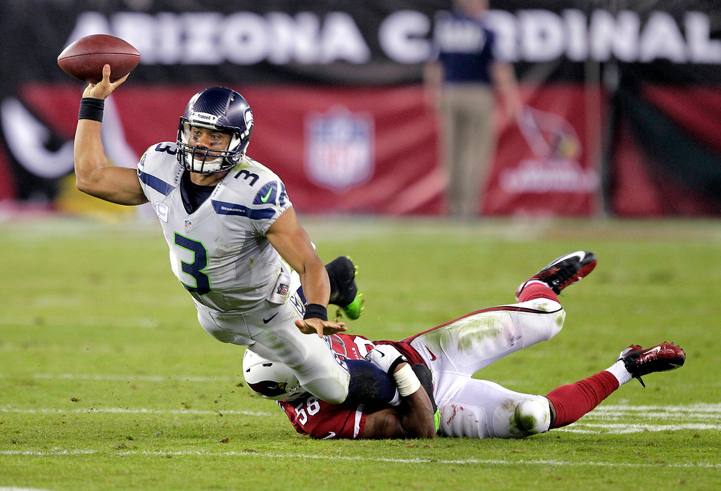 . Seattle Seahawks quarterback Russell Wilson (3) gets a pass off as Arizona Cardinals inside linebacker Karlos Dansby (56) brings him down during the second half of an NFL football game, Thursday, Oct. 17, 2013, in Glendale, Ariz. (AP Photo/Rick Scuteri)