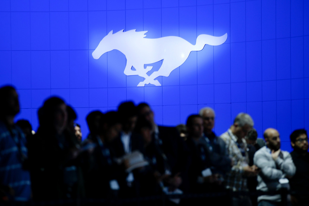 . The Ford Mustang logo is displayed behind people gathering for the unveiling of the new Ford Edge concept vehicle at the Los Angeles Auto Show on Wednesday, Nov. 20, 2013, in Los Angeles. (AP Photo/Jae C. Hong)
