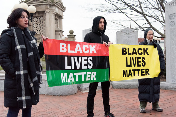12/14/18 Wesley Bunnell | Staff Activists and family members spoke on Friday afternoon at Central Park, across from city hall, in remembrance of the police involved shooting on Chapman St one year ago. Activists stand with Black Lives Matter banners during the vigil.