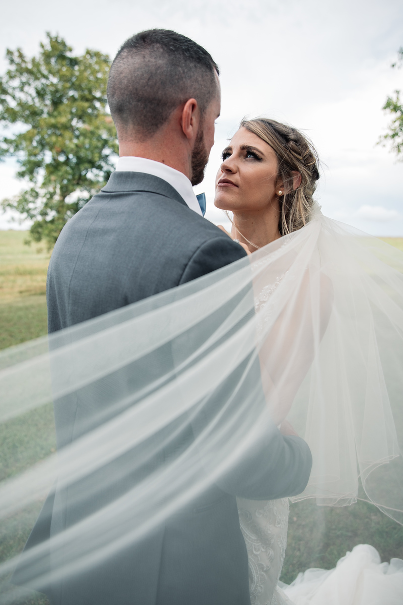 a bride staring into her grooms eyes with her vale wrapping in the wind