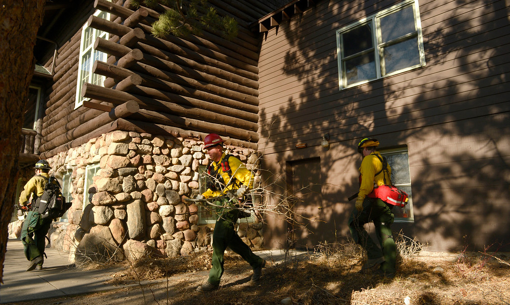 . Wildland firefighters from Lafayette Fire clear brush and debris from the Moraine Park Vistor\'s Center to protect the structure just in case the fire reaches the building on December 2nd, 2012.