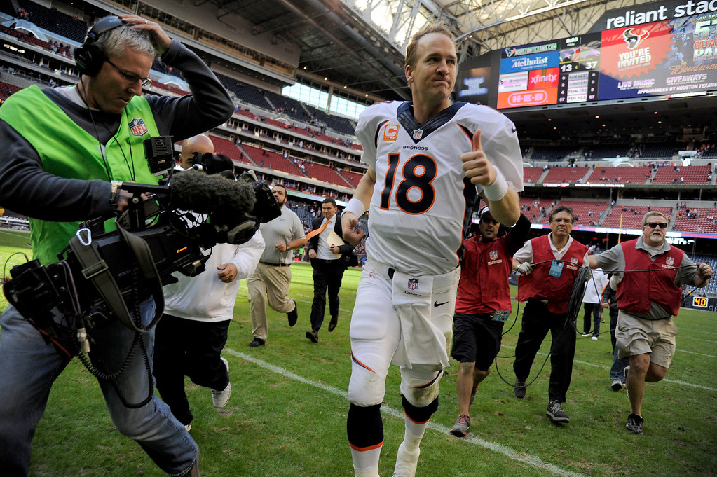 . Denver Broncos quarterback Peyton Manning (18) gives a thumbs up as he runs off the field after their win over the Houston Texans 37-13 December 22, 2013 at Reliant Stadium. (Photo by John Leyba/The Denver Post)