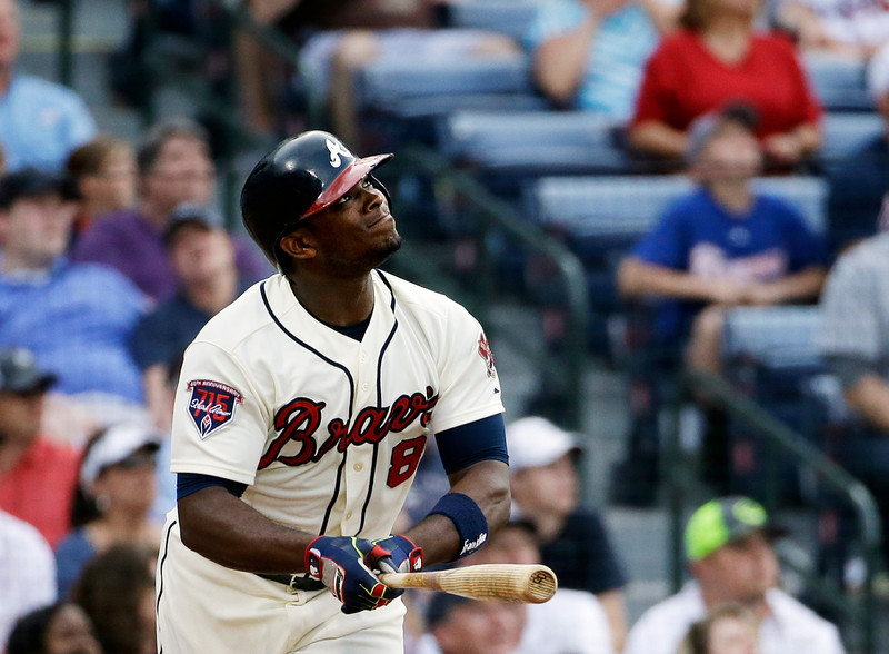 . Atlanta Braves\' Justin Upton watches the flight of his ball after hitting a sacrifice fly to score teammate B.J. Upton in the eighth inning of a baseball game against the Colorado Rockies, Saturday, May 24, 2014, in Atlanta. (AP Photo/David Goldman)