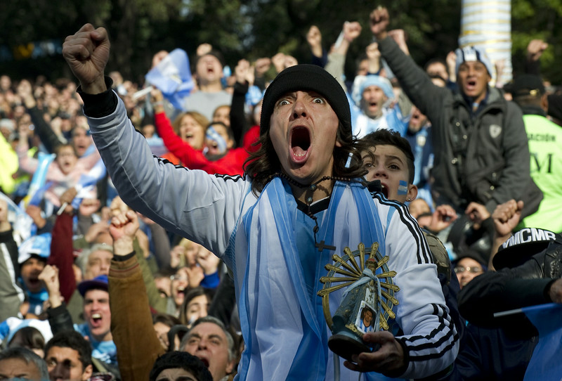 . An Argentine fan celebrates as he holds an image of the Lujan Virgin with a picture of Argentinian football star Lionel Messi while watching the FIFA World Cup Brazil 2014 match against Nigeria on a giant screen at San Martin Square, in Buenos Aires, on June 25, 2014.  (ALEJANDRO PAGNI/AFP/Getty Images)
