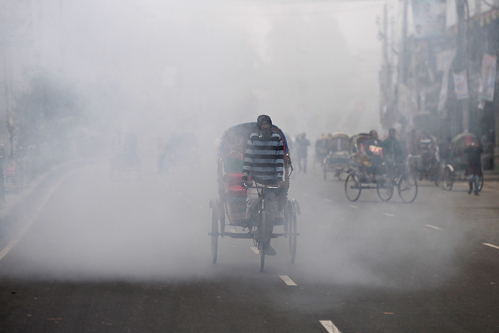 . A bangladeshi rickshaw puller cycles past the cloud of a smoke bomb during a nationwide strike in Dhaka on December 11, 2012.  Bangladesh was shut down for a second day in less than a week as the opposition parties enforced a nationwide strike demanding early elections under a neutral caretaker government. MUNIR UZ ZAMAN/AFP/Getty Images