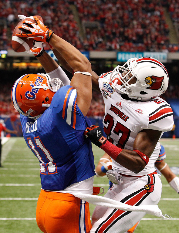 . Louisville safety Jermaine Reve (27) breaks up a pass in the end zone to Florida tight end Jordan Reed (11) in the first half of the Sugar Bowl NCAA college football game Wednesday, Jan. 2, 2013, in New Orleans. (AP Photo/Bill Haber)