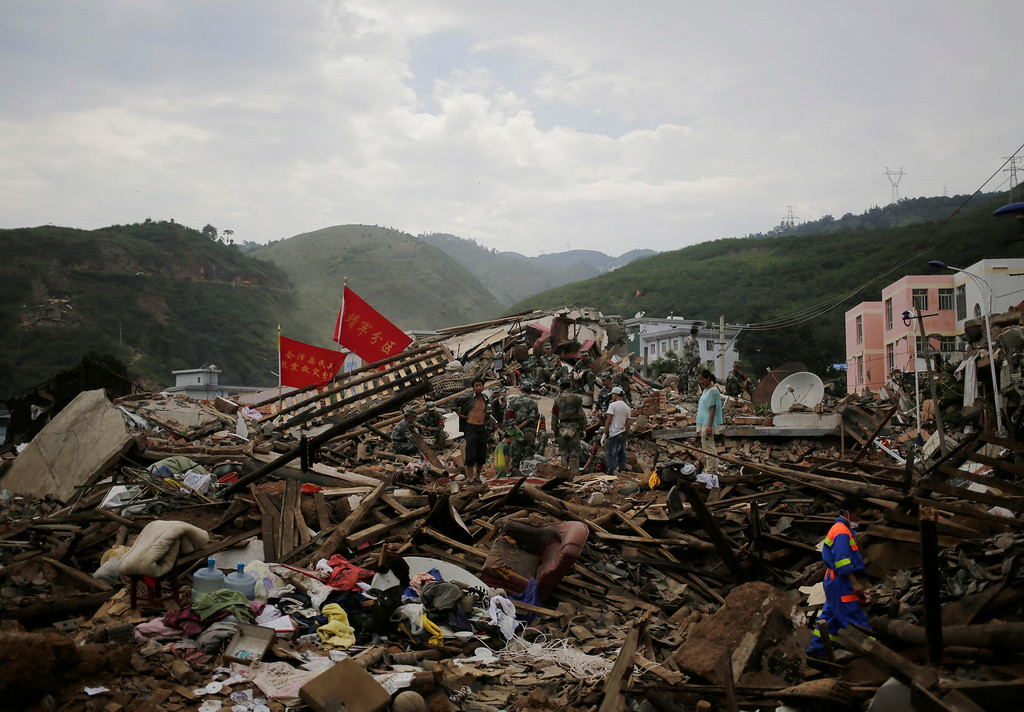 . A rescuer walks past paramilitary policemen searching for survivors at a destroyed house following a massive earthquake in the town of Longtoushan in Ludian County in southwest China\'s Yunnan Province Tuesday, Aug. 5, 2014.  (AP Photo/Andy Wong)