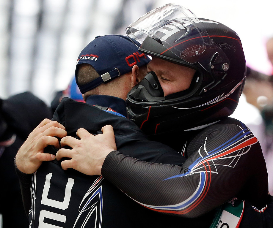 . The driver of United States USA-1, Steven Holcomb, hugs a coach after the team won the bronze medal during the men\'s four-man bobsled competition final at the 2014 Winter Olympics, Sunday, Feb. 23, 2014, in Krasnaya Polyana, Russia. (AP Photo/Dita Alangkara)