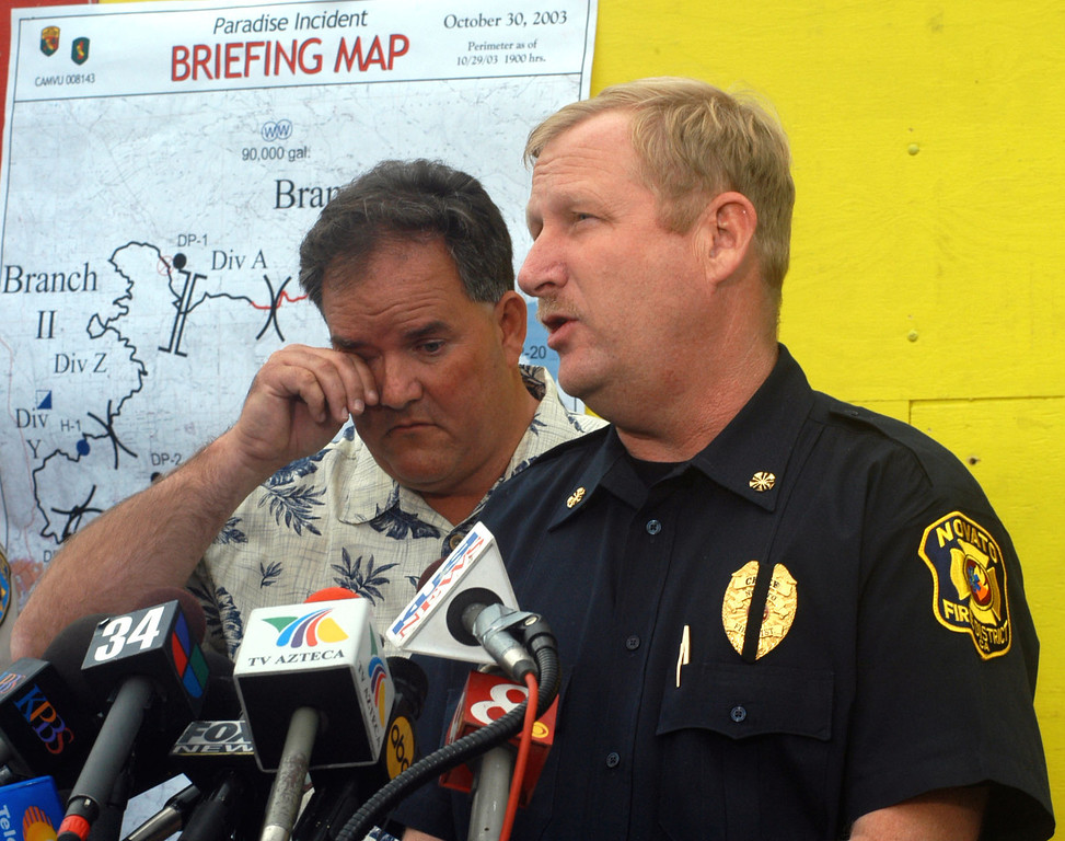 . Novato Fire Chief Jeff Meston, right, speaks during a news conference, Thursday, Oct. 30, 2003, in El Cajon, Calif., as Brad Beedle,left, president of the Novato Board of Fire Protection District, rubs his eye. Steve Rucker, a 38-year-old fire engineer, died Wednesday while battling the Cedar Fire in San Diego County.   Rucker was part of a fire engine crew from the Novato Fire Protection District, just north of San Francisco, that was trying to save a mountain home near Wynola. (AP Photo/Joan C. Fahrenthold)
