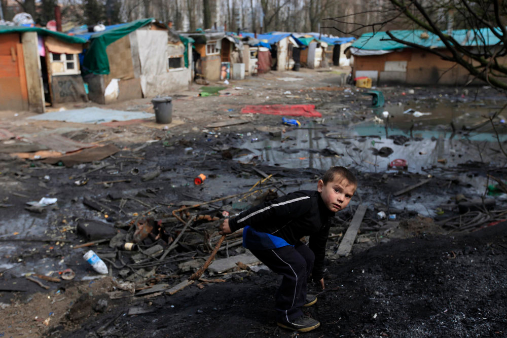 . A Roma boy plays front of shelters in an illegal camp in Lille, northern France on International Roma Day on April 8, 2013.   REUTERS/Pascal Rossignol