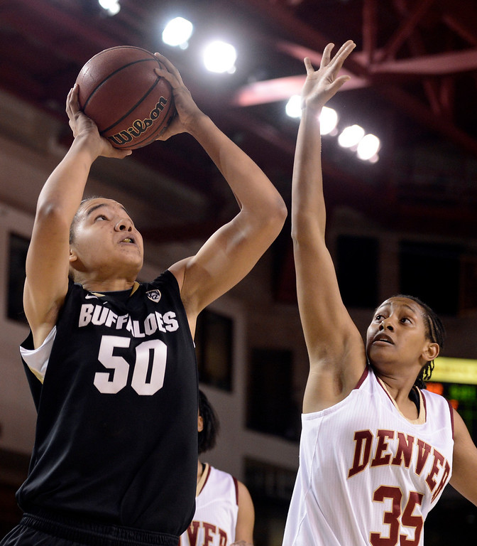 . University of Colorado\'s Jamee Swan takes a shot over Desiree Hunter during a games against the University of Denver on Tuesday, Dec. 11, at the Magnus Arena on the DU campus in Denver.   (Jeremy Papasso/Daily Camera)