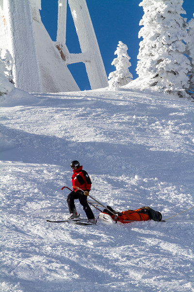 A ski patrol technician brings down an injured skier on a gurney past snow swept trees and towers