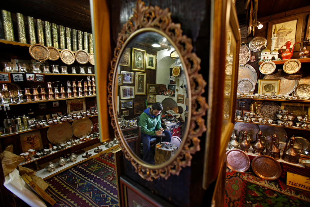 ". In this Tuesday, May 6, 2014 photo, a Bosnian man produces hand made souvenirs in a shop in the old town, known as Bascarsija, in Sarajevo, Bosnia-Herzegovina. Despite the dark chapters of the past, today the city is defined by what locals call ""the Sarajevo Spirit\"", an interesting and mostly harmonious mix of religions and cultures. (AP Photo/Amel Emric)"