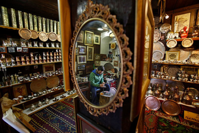 """. In this Tuesday, May 6, 2014 photo, a Bosnian man produces hand made souvenirs in a shop in the old town, known as Bascarsija, in Sarajevo, Bosnia-Herzegovina. Despite the dark chapters of the past, today the city is defined by what locals call \""""the Sarajevo Spirit\"""", an interesting and mostly harmonious mix of religions and cultures. (AP Photo/Amel Emric)"""
