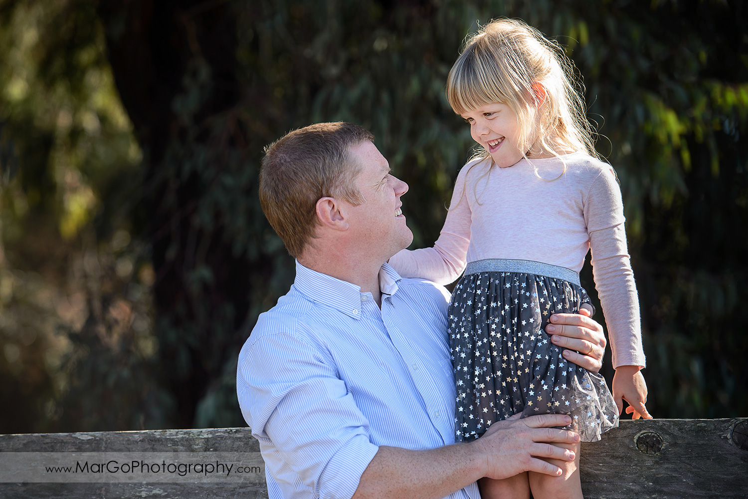 portrait of the little girl in navy blue skirt with golden stars and her dad at Mountain View Shoreline Lake Park
