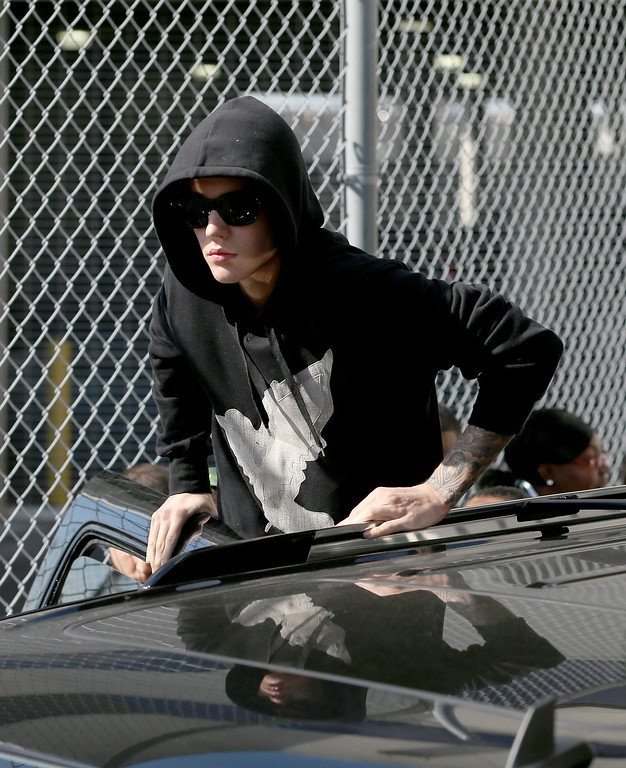 . Justin Bieber prepares to stand on his vehicle after exiting from the Turner Guilford Knight Correctional Center on January 23, 2014 in Miami, Florida. Justin Bieber was charged with drunken driving, resisting arrest and driving without a valid license after Miami Beach police found the pop star street racing Thursday morning.  (Photo by Joe Raedle/Getty Images)