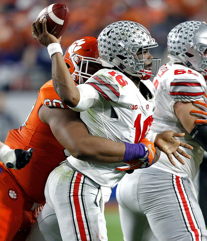 . Ohio State quarterback J.T. Barrett (16) is hit by Clemson defensive tackle Dexter Lawrence during the first half of the Fiesta Bowl NCAA college football game, Saturday, Dec. 31, 2016, in Glendale, Ariz. (AP Photo/Ross D. Franklin)