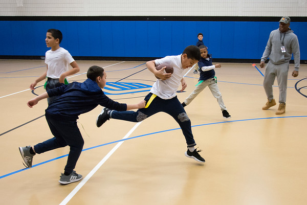 02/18/20 Wesley Bunnell | StaffrrKids play a game of indoor touch football in the gymnasium at the New Britain Boys and Girls Club on Tuesday afternoon. Jonathan Martinez, age 10, tries to avoid the defense as he runs down the middle with the ball.