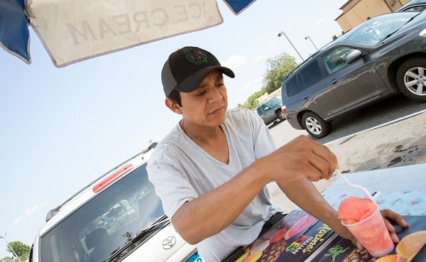 08/19/19 Wesley Bunnell | Staff Alejandro Pineda serves italian ice from his stand near New Brite Plaza on Monday August 19, 2019.