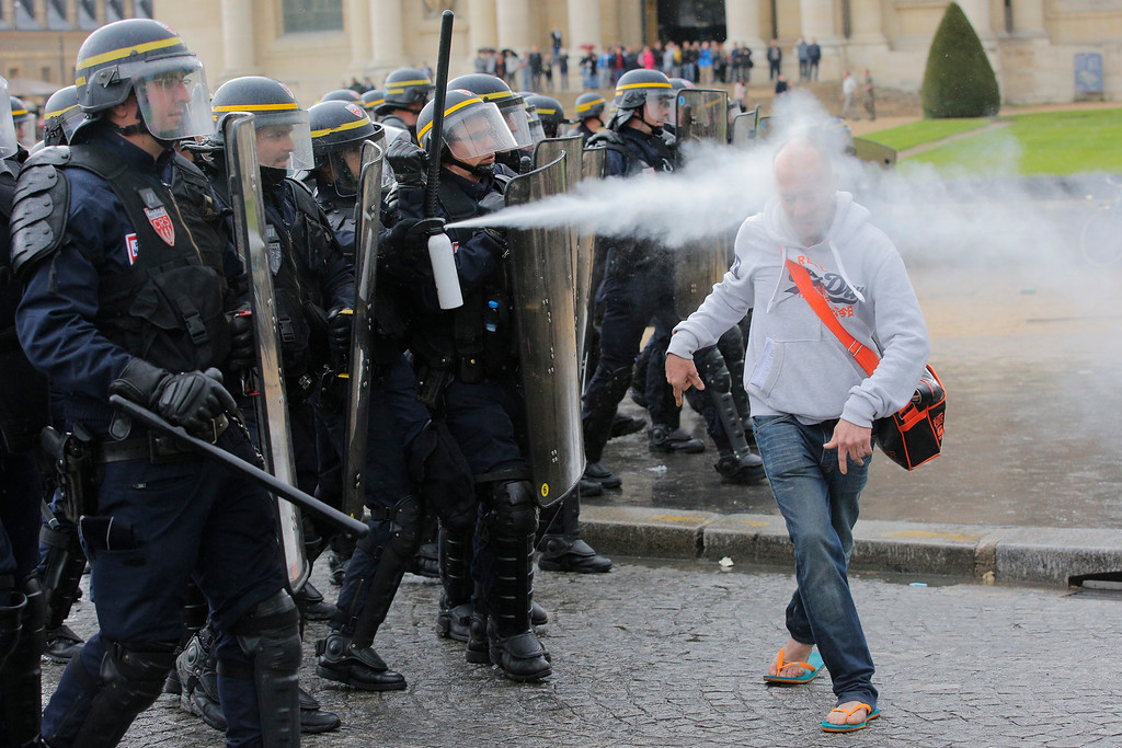 . French riot police officers sprays pepper gas at a demonstrator during a protest against Labor Law as the Socialist government decided to force the bill through Parliament without a vote, in Paris, Thursday, May 12, 2016. France\'s government is facing a major test as lawmakers hold a no-confidence vote, prompted by a deeply divisive labor law allowing longer workdays and easier layoffs. (AP Photo/Christophe Ena)