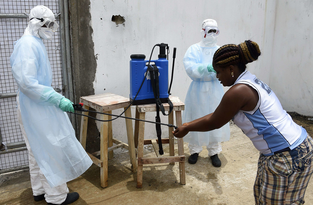 . A visitor\'s hands are decontaminated by health workers at Island Hospital as she arrives to deliver food to relatives suffering from the Ebola virus in Monrovia on September 26, 2014PASCAL GUYOT/AFP/Getty Images