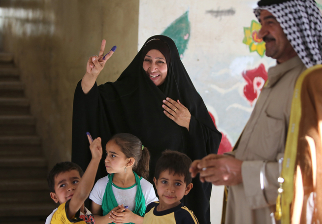Description of . An Iraqi woman and her children display ink-stained fingers after she cast her ballot in Baghdad's Sadr City district during her country's general elections on April 30, 2014. Iraqis streamed to voting centres nationwide, amid the worst bloodshed in years, as Prime Minister Nuri al-Maliki seeks reelection.  (AHMAD AL-RUBAYE/AFP/Getty Images)