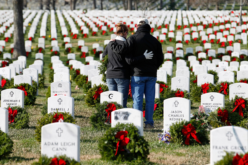 . Volunteers pauses over the grave of a fallen soldier after laying a holiday wreaths, during Wreaths Across America Day at Arlington Cemetery on Saturday Dec. 10, 2011. wld,(AP Photo/Jose Luis Magana)