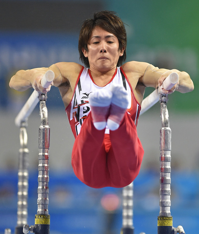 . Japan\'s Ryohei Kato performs on the parallel bars during the men\'s team final of the Gymnastics World Championships in Nanning, in China\'s southern Guangxi province on October 7, 2014. KAZUHIRO NOGI/AFP/Getty Images