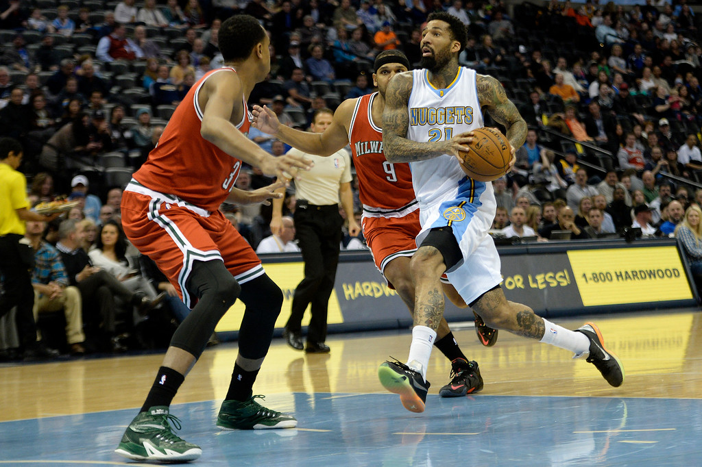 . DENVER, CO - MARCH 03: Wilson Chandler (21) of the Denver Nuggets drives agains the defense of John Henson (31) of the Milwaukee Bucks and Jared Dudley (9) during the first quarter of action. The Denver Nuggets hosted the Milwaukee Bucks at the Pepsi Center on Tuesday, March 3, 2015. (Photo by AAron Ontiveroz/The Denver Post)