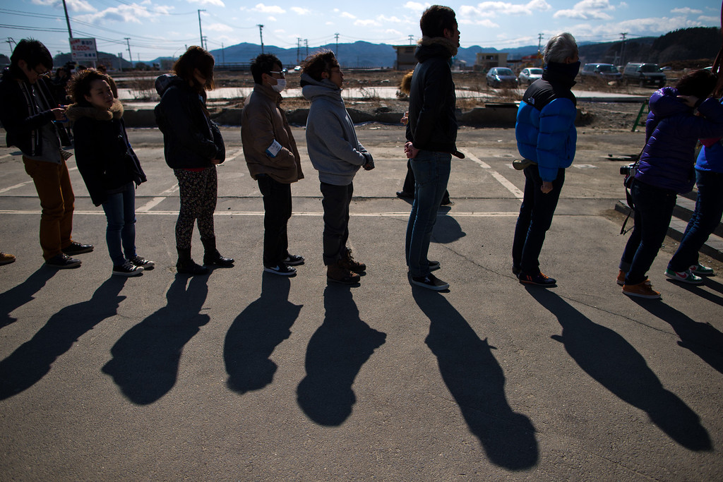 . Japanese people line up to pay their respect in front of the remaining structure of a former disaster center to commemorate the second anniversary of the Great East Japan Earthquake and Tsunami on March 11, 2013 in Minamisanriku, Miyagi Prefecture, Japan. Japan is commemorating the second anniversary of the 2011 Magnitude 9.0 earthquake and subsequent tsunami that claimed more than 18,000 lives.  (Photo by Athit Perawongmetha/Getty Images)