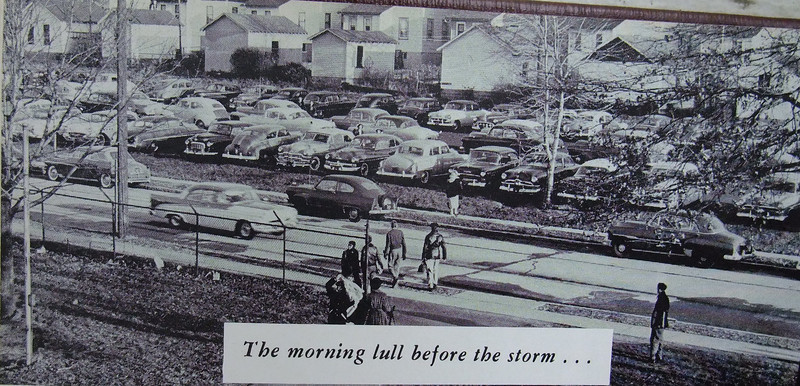 Extra large cars add to the parking lot congestion on Stone St. in this 1956 yearbook photo. The backs of the garages and houses that sit on Wooley ave. are in the background.