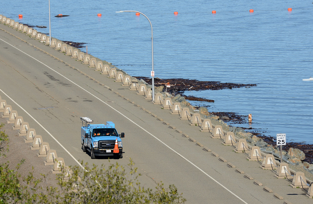 . A PG&E pickup drives across the Oroville Dam as water flows over the emergency spillway Saturday, Feb. 11, 2017, and in the main spillway in Oroville, California. (Dan Reidel -- Enterprise-Record)