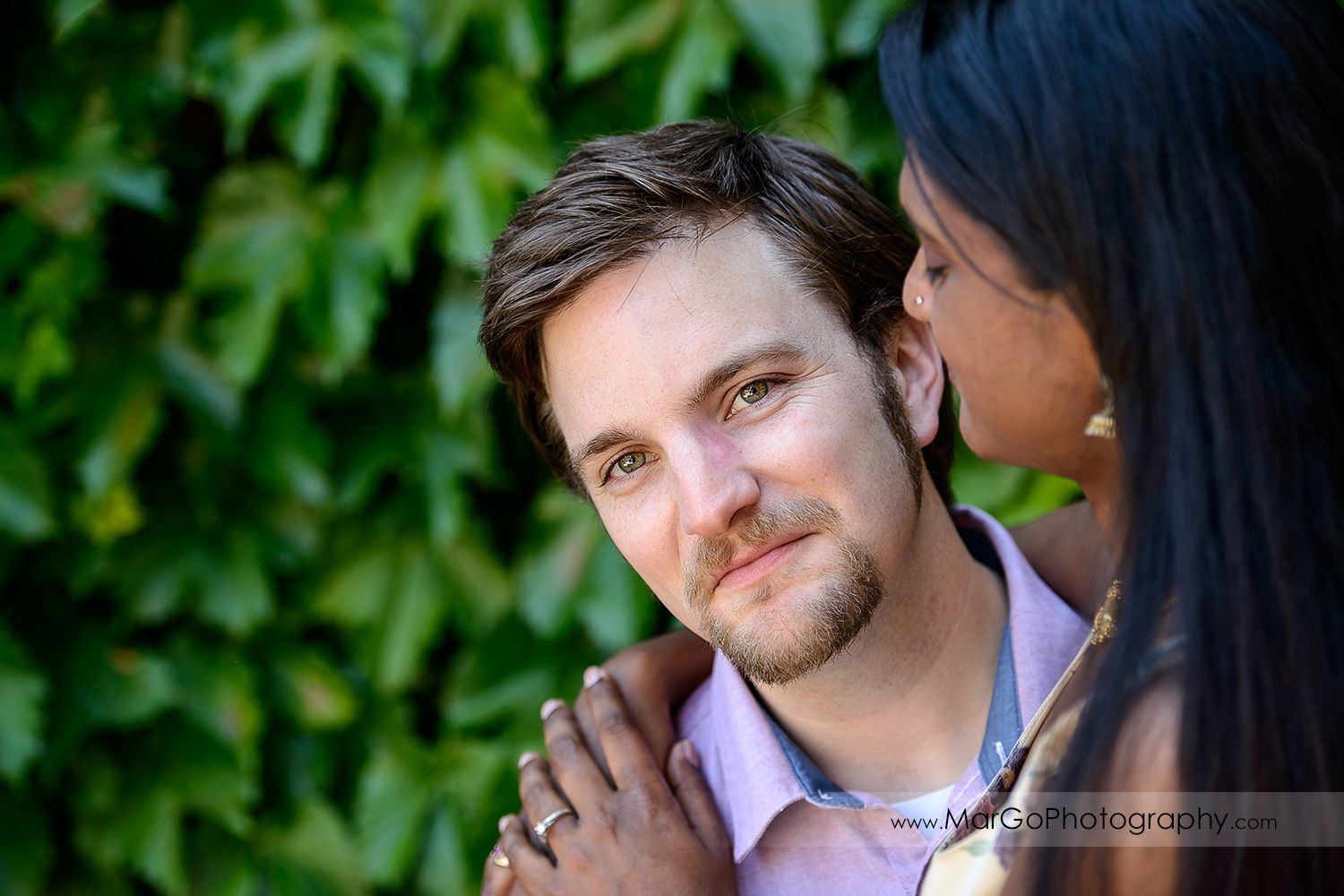 portrait of man in pink shirt through Indian woman in flower dress during engagement session at Castello di Amorosa in Calistoga