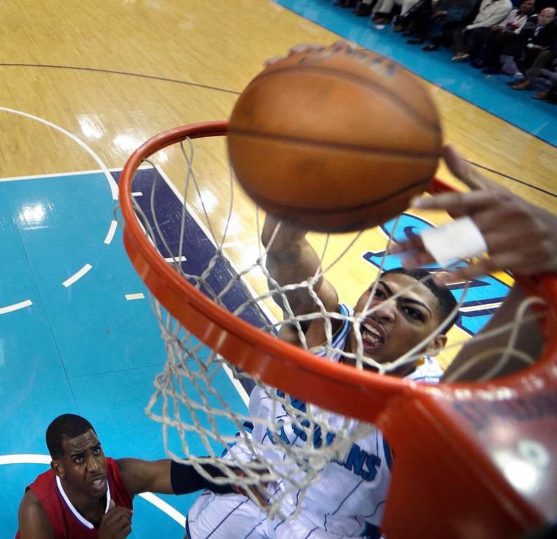. New Orleans Hornets forward Anthony Davis, right, dunks over Los Angeles Clippers guard Chris Paul in the first half of an NBA basketball game in New Orleans, Wednesday, March 27, 2013. (AP Photo/Gerald Herbert)